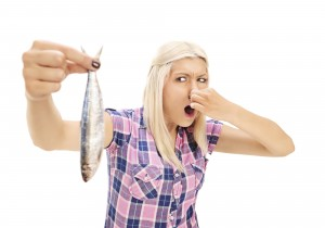 Blond woman holding a stinky fish isolated on white background