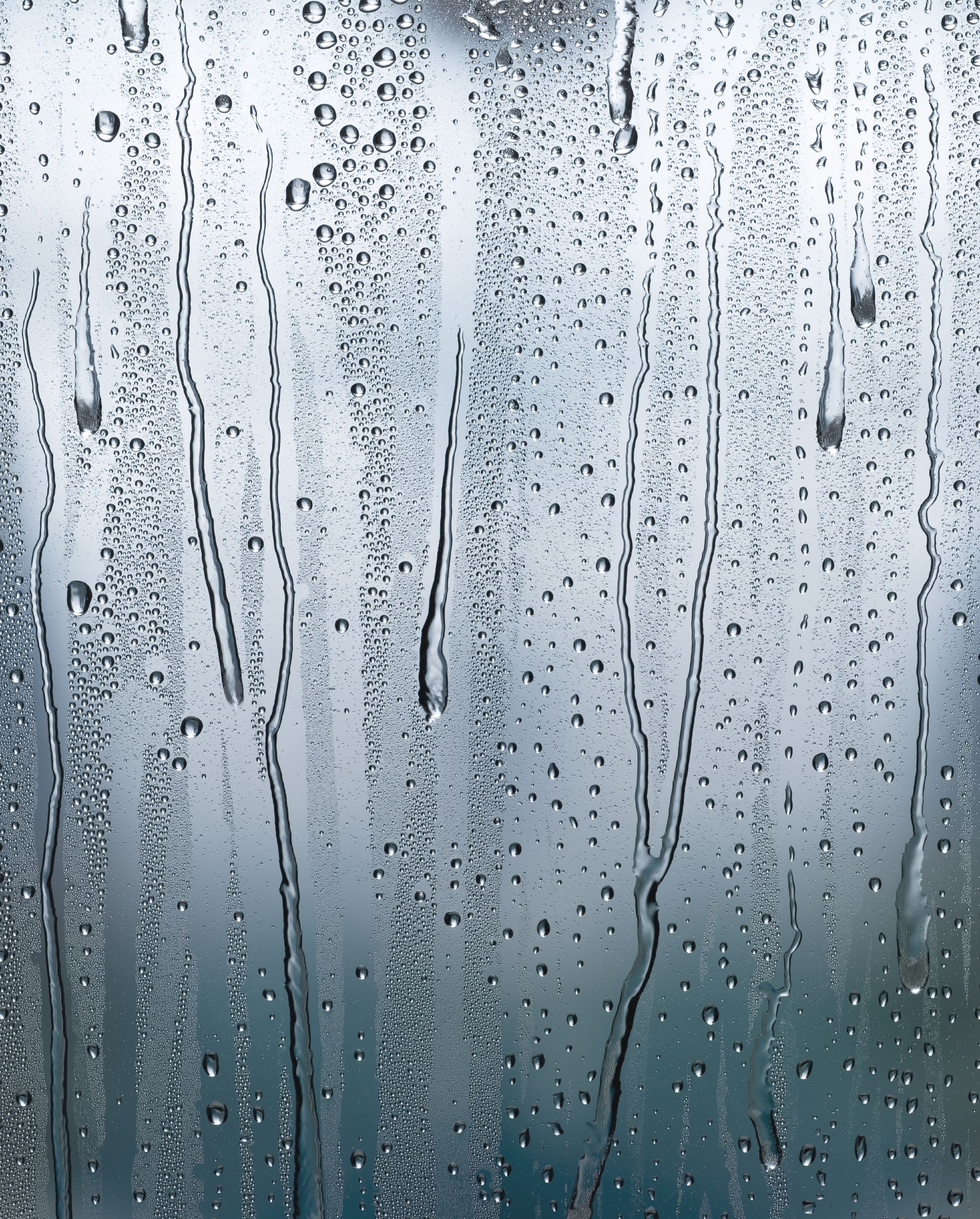 Condensation runs down a window pane in front of a blurred image of the outside. Stitched image from two files