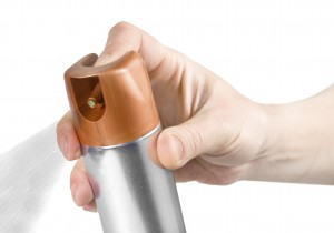 Upper part of aluminum spray bottle and a hand pushing the button.